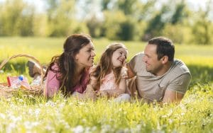 Happy mid adult parents talking to their little daughter while being on picnic during spring day.